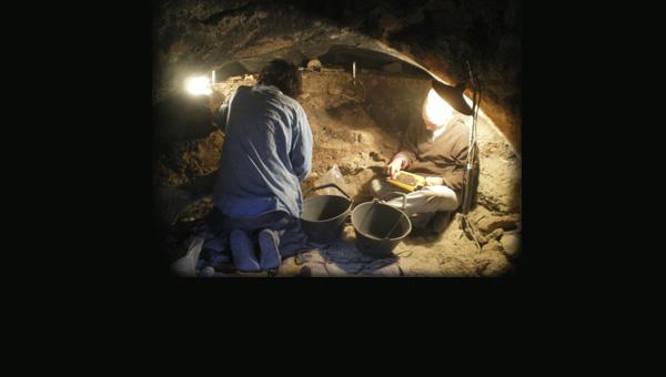 Arqueólogos excavando una cueva muy obscura y colmatada de sedimentos.